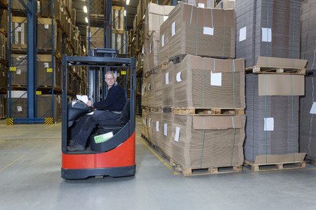 Man driving a reach truck trough a warehouse. He is driving alongside a decent row of cartboard boxes.  photo