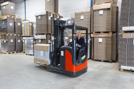 Reach truck passing by in a warehouse where cartboard boxes are stored on palets.