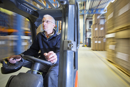forklift driver: Rig shot of a forklift driver, steering his vehicle through a warehouse, with vast motion blur in the background Stock Photo
