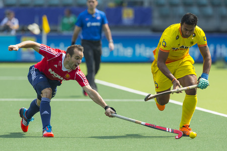 englishman: THE HAGUE, NETHERLANDS - JUNE 2: Englishman Catlin reaches for the ball to stop a rush by Indian player Raghunath  during the Hockey World Cup 2014 in the match between England and India (men). GBR beats IND 2-1 Editorial