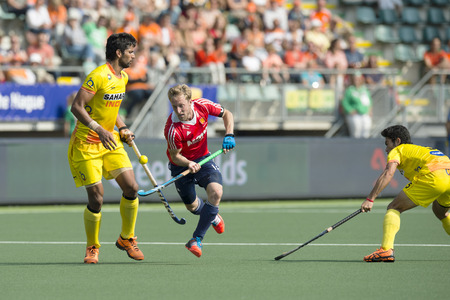 THE HAGUE, NETHERLANDS - JUNE 2: English player Barry Middleton (middle) lifts the ball high on his stick, passing Indian player Rupinder at the Rabobank World Cup Hockey. England Beats India 2-1 Editorial
