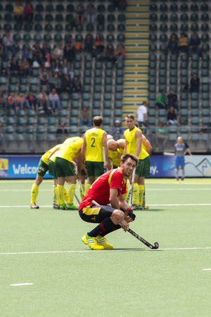 THE HAGUE, NETHERLANDS - JUNE 2: Manel Terraza (Spain) squats down in disappointment after losing the match against Australia (huddling in the background) with 3-0 at the Rabobank World Cup Hockey