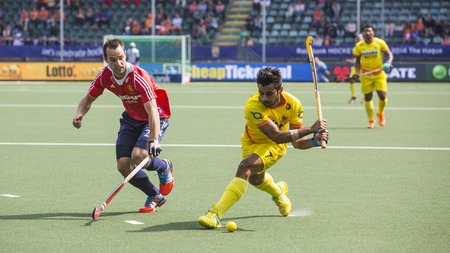 englishman: THE HAGUE, NETHERLANDS - JUNE 2: Englishman Catlin reaches for the ball to stop a rush by Indian player manpreet during the Hockey World Cup 2014 in the match between England and India (men). GBR beats IND 2-1 Editorial