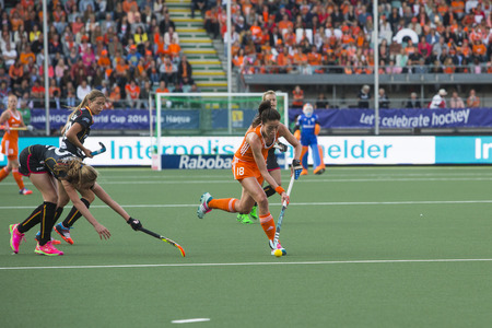 preliminary: THE HAGUE, NETHERLANDS - JUNE 2: Dutch van As is passing the Belgium defense of the Belgium team during the Hockey World Cup 2014 in the preliminary match between The Netherlands and Belgium (woman) NED beats BEL 4-0 Editorial