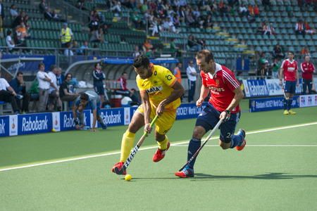 englishman: THE HAGUE, NETHERLANDS - JUNE 2: Englishman Catlin reaches for the ball to stop a rush by Indian player Raveendran  during the Hockey World Cup 2014 in the match between England and India (men). GBR beats IND 2-1 Editorial