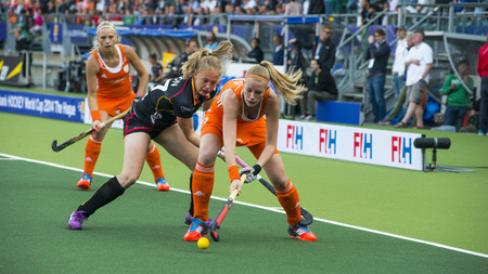 jill: THE HAGUE, NETHERLANDS - JUNE 2: Dutch Maasakker is is playing the ball when Belgium player Boon is trying to take over the ball. During the Hockey World Cup in the prelimiary match between The Netherlands and Belgium (woman) NED beats BEL 4-0 Editorial