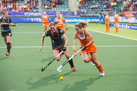 b ball: THE HAGUE, NETHERLANDS - JUNE 2: Dutch Hoog is lifting her stick to control the ball, Belgium player de Groof is trying to take over the ball during the Hockey World Cup 2014 in the preliminary match between The Netherlands and Belgium (woman) NED beats B