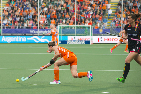 attacker: THE HAGUE, NETHERLANDS - JUNE 2: Dutch Jonker is passing the ball Belgium player De Groof is right behind her during the Hockey World Cup 2014 in the preliminary match between The Netherlands and Belgium (woman) NED beats BEL 4-0