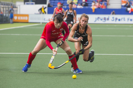 preliminary: THE HAGUE, NETHERLANDS - JUNE 2: New Zealander Webster is trying to take the ball from Korean Lee during the Hockey World Cup 2014 in the preliminary match between Korea and New Zealand (woman). KOR beats NZL  1-0
