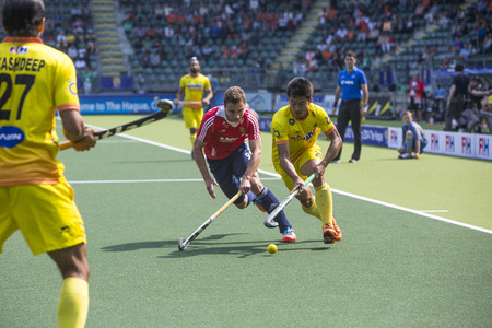 englishman: THE HAGUE, NETHERLANDS - JUNE 2: Englishman Martin is trying to block Indian player Kangujam during the Hockey World Cup 2014 in the match between England and India (men). GBR beats IND 2-1
