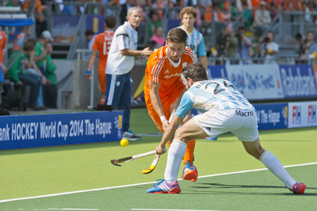 duelling: THE HAGUE, NETHERLANDS - JUNE 2: Argentinian Brunet tries to block Netherlands player Kemperman lifts the ball and passes him, at the World Cup Hockey. NED beats ARG 3-1 Editorial