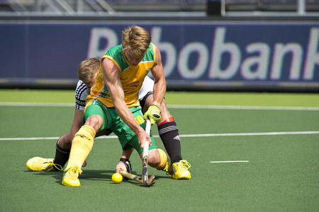 ger: HE HAGUE, NETHERLANDS - JUNE 1: Two unidentified field hockey players fight for posession over the ball during the match between Germany and South Africa at the World Cup Hockey 2014. Germany wins 4-0