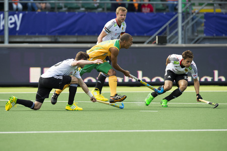 ger: THE HAGUE, NETHERLANDS - JUNE 1: South African Hockey Player Julian HykesIs being stopped by two German defenders during the World Cup Hockey. GER-RSA 4-0