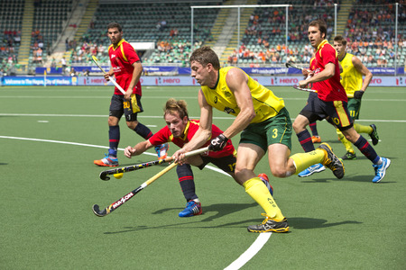 esp: THE HAGUE, NETHERLANDS - JUNE 2: Simon Orchard (AUS) lifts the ball, entering the Spanish circle whilst Ramon Alegre (ESP) vigorously defends  during the Hockey World Cup 2014 in the match between Australia and Spain. AUS beats SPA 3-0 Editorial