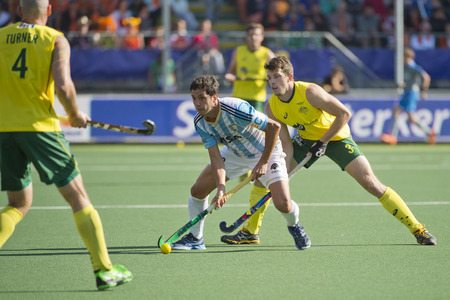 attacker: THE HAGUE, NETHERLANDS - JUNE 13: Australian Orchard challenges Argentinian Captain Rey for the ball during the semi finals match of the World Championships hockey 2014