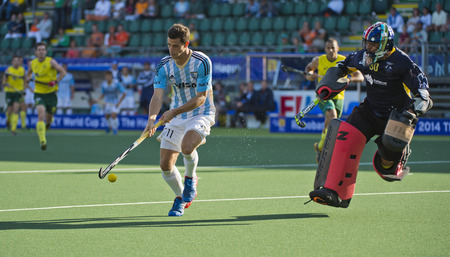 THE HAGUE, NETHERLANDS - JUNE 13: Argentinian Joaquin Menini controlls the ball after a counter, ending up one on one with the Australian Goalie Adrew Carter during the Semi-Finals of the World Cup Hockey 2014