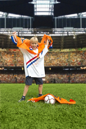 Young boy, rasing his hands in victory, wearing a flag in a huge, packed stadium photo