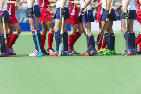 Fair Play concept for sportsmanship, showing two oppsing teams of women field hockey players shaking hands after the line-up of an important match.