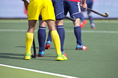 Hockey players from two different teams guarding during a match on an artificial grass pitch photo