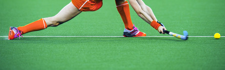 Female athlete field hockey player performing a stretched drag flick on an artificual grass pitch