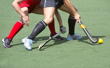 hockey sobre cesped: Cerca de dos jugadores de hockey hierba, desafiando a nosostros para el control y la posesi�n de la pelota durante un partido intenso, competitivo a nivel profesional