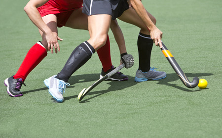 Close up of two field hockey players, challenging eachother for the control and posession of the ball during an intense, competitive match on professional level photo