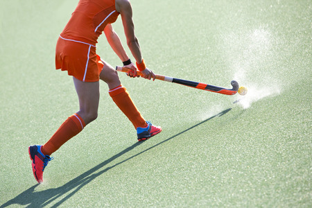 Female field hockey player passing to a team mate on a modern, water artificial field Фото со стока