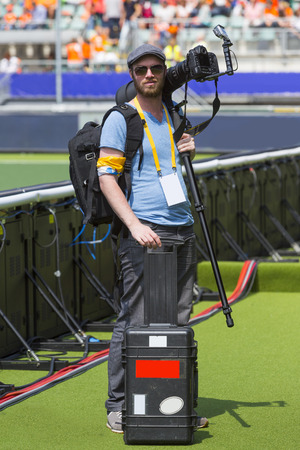 photojournalist: A sports photographer posing along a sportsfield with his camera on his shoulder with a monopod mounded on it, in his other hand he hold a case for the other lenses.  Stock Photo
