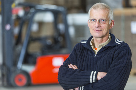 forklift driver: A forklift driver is posing in front of his forklift, he is a proffesional forkliftdriver, working in a warehouse.