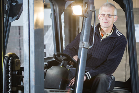 forklift: Expreinced forklift driver is posing inside his forklift in a warehouse Stock Photo