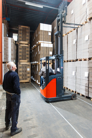 Supervizor oversees a pallettruck reaching high up while grabbing a pallet from the top shelf photo