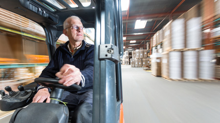 Elderly man driving a forklift trough a warehous where cardboard boxes are stored.