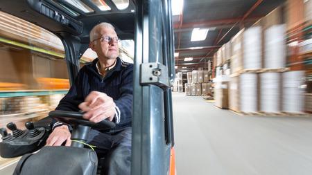 Vieil homme au volant d'une auge chariot élévateur un warehous où des boîtes de carton sont stockés.
