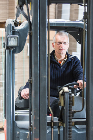 just in time: Forklift driver, manning the controls and steering wheel of his forklift in a large warehouse. Just in Time concept Stock Photo