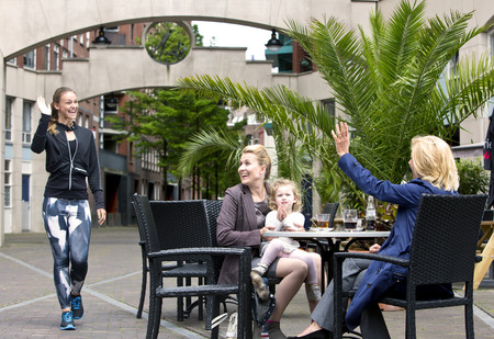 encounter: A group of three, very diverse women, meeting on a terrace. A sporty jogging woman waves at a senior lady, with a mother and her young daughter also sitting at the table in an urban setting.
