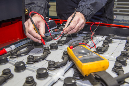 Man, checking the nodes of the battery pack of a forklift, using a multimeter Stock Photo