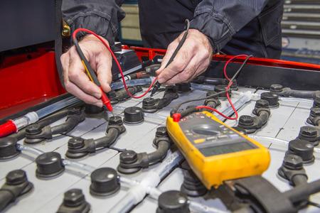 Mann, der Überprüfung der Knoten des Batteriepacks mit einem Gabelstapler, mit einem Multimeter Standard-Bild - 29942457