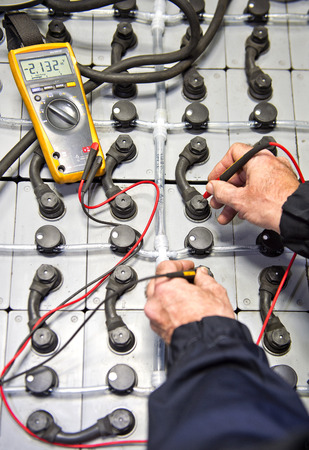 closed circuit: Mechanic, checking the health of a large battery pack using a multimeter