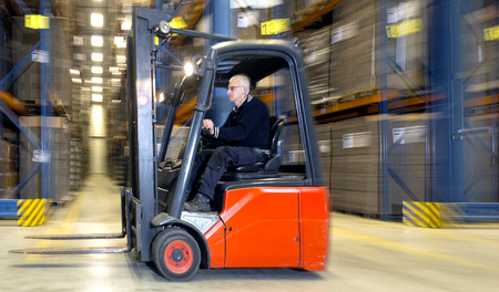 Forklift in a warehouse, driving at speed past the aisles of storage racks Stock Photo