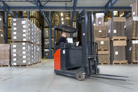 backing up: Reach truck driving around cartboard boxes in a warehouse.