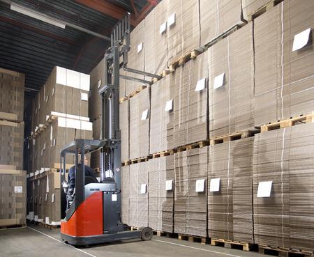 montacargas: Alcance carretilla elevadora levantar un pallet con materiales sobrantes de la plataforma superior en un gran almacén.