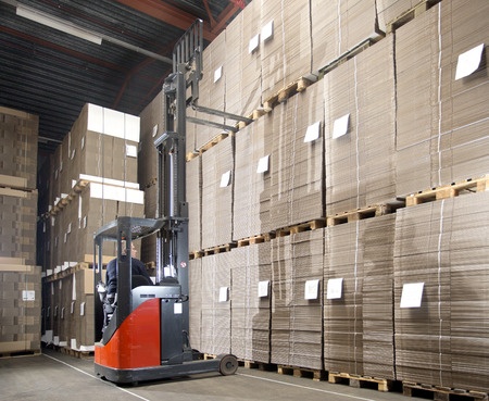 hydraulic lift: Reach truck forklift lifting a pallet with surplus materials from the top shelf in a large warehouse. Stock Photo