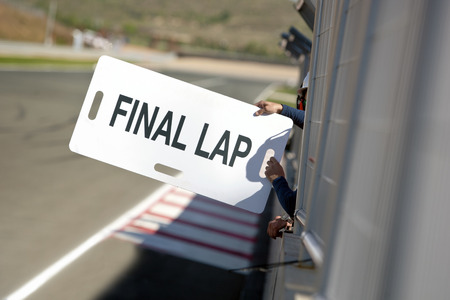 Man, holding out a notice board, informing their race car driver of the Final Lap, through the fences surrounding the pit lane along the final straight stretch of a race circuit