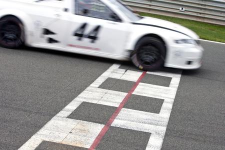 Voiture de course de franchir la ligne d'arrivée sur un circuit