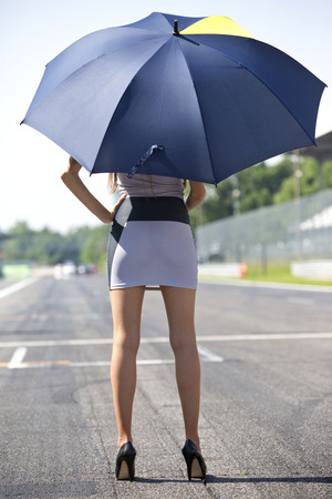 race relations: Long legged grid girl standing on the grid of a circuit, holding an umbrella