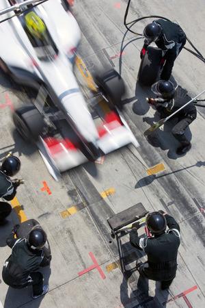 pit stop: Equipo de mec�nicos profesionales listos para la acci�n como coche de carreras de su equipo llega a la calle de boxes durante una Pitsstop de una carrera de autos, el concepto de trabajo en equipo definitivo Foto de archivo