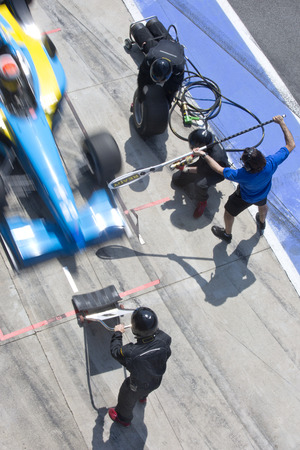 fast lane: Equipo de mec�nicos profesionales listos para la acci�n como coche de carreras de su equipo llega a la calle de boxes durante una Pitsstop de una carrera de autos, el concepto de trabajo en equipo definitivo Foto de archivo