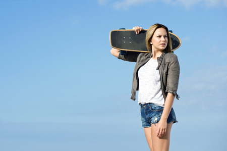 Pretty girl carrying a skateboard on her shoulder, looking back. Plenty of copy space. photo