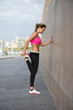 running pants: Lean, muscular and athletic woman stretching her thighs as part of her warming up during a training run