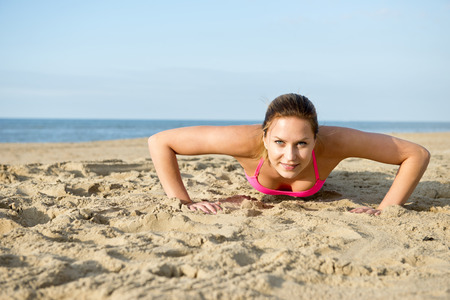 excersise: Fit, athletic, woman doing push ups during a workout on a sandy beach Stock Photo